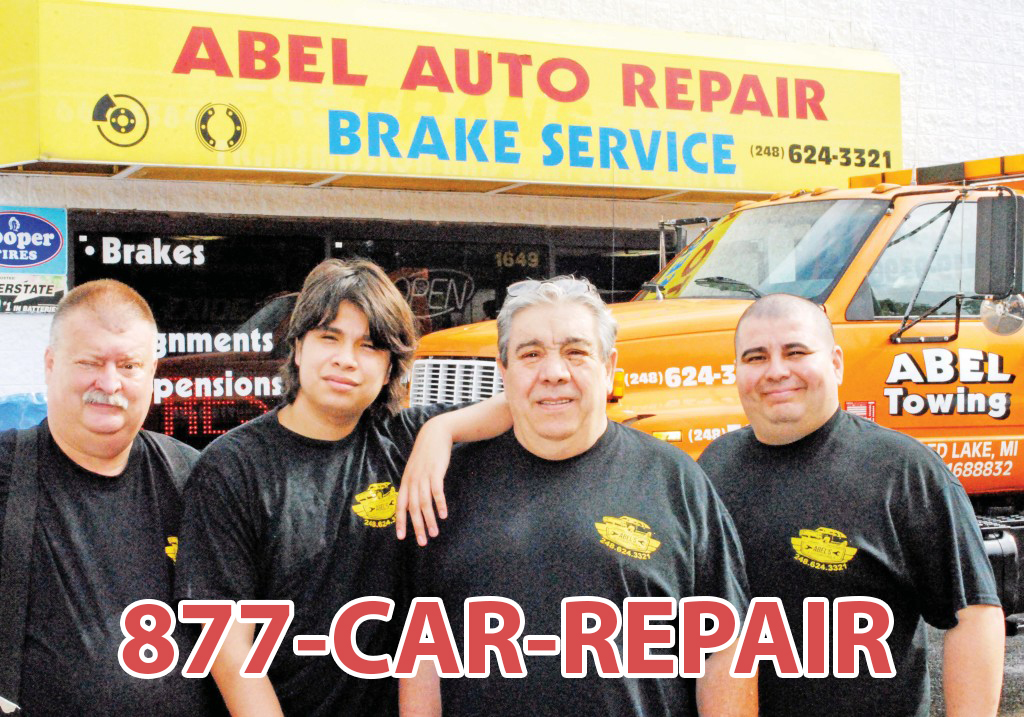 Four guys standing in front of a car repair shop using 1-877-CAR-REPAIR
