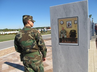 soldier dressed in uniform reading a sign at the wreath laying ceremony
