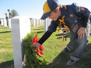 Young cub scout laying a wreath at a cemetary headstone